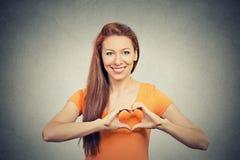 Femme heureuse gaie de sourire de portrait faisant le signe de coeur avec des mains Image libre de droits