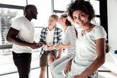 Femme heureuse gaie se tenant ainsi que ses collègues Image stock