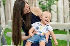 Femme heureuse jouant avec le bébé cet emplacement sur ses genoux photographie stock