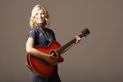 Femme heureuse jouant la guitare photo stock