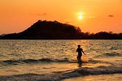 Femme heureuse jouant sur la plage au temps de coucher du soleil Photographie stock