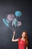Femme heureuse jugeant des ballons dessinés sur le fond de tableau noir Photo stock