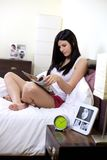 Femme heureuse à la maison détendant la magazine de lecture dans le lit Photographie stock