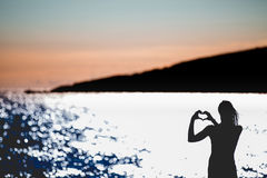 Femme heureuse libre appréciant le coucher du soleil Embrassant la lueur de soleil du coucher du soleil d'or, appréciant la paix, Images stock