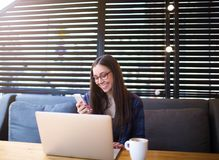 Femme heureuse lisant le bon message textuel dans le réseau social par l'intermédiaire du téléphone de cellules, se reposant avec photo stock