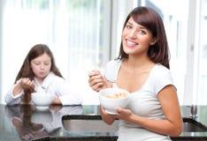 Femme heureuse mangeant de la céréale de petit déjeuner avec le descendant photographie stock libre de droits