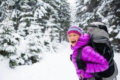 Femme heureuse marchant dans la forêt d'hiver avec le sac à dos photographie stock