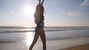 Femme heureuse marchant et tournant sur la plage près de l'océan Jeune belle fille appréciant la vie et ayant l'amusement en mer banque de vidéos