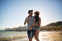 Femme heureuse marchant sur la plage avec l'ami l'embrassant Image stock