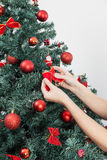Femme heureuse mettant un arc dans l'arbre de Noël Images stock