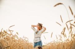 Femme heureuse mignonne sur le champ de blé d'été Photographie stock