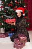 Femme heureuse montrant des cadeaux de Noël Photographie stock libre de droits