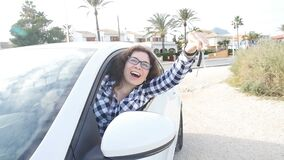 Femme heureuse montrant la clé de la nouvelle voiture dehors banque de vidéos