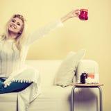 Femme heureuse montrant la tasse de thé images stock