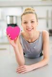 Femme heureuse montrant le coeur décoratif dans la cuisine Photos stock
