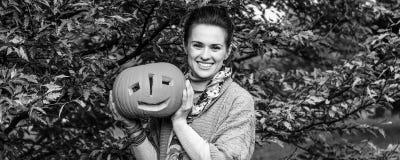 Femme heureuse montrant le potiron Jack OLantern de Halloween Image stock