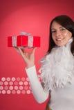 Femme heureuse montrant un cadeau rouge de Noël Photographie stock libre de droits