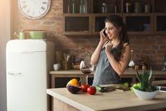 Femme heureuse parlant au téléphone dans la cuisine à la maison image libre de droits