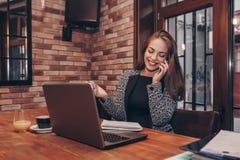 Femme heureuse parlant au téléphone et à l'aide d'un ordinateur portable photographie stock libre de droits