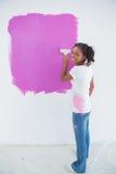 Femme heureuse peignant son mur dans le rose lumineux photo libre de droits