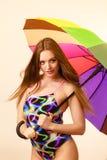 Femme heureuse posant dans le maillot de bain et le parapluie coloré image stock