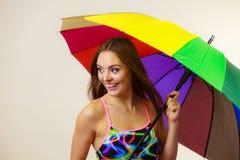 Femme heureuse posant dans le maillot de bain et le parapluie coloré images libres de droits