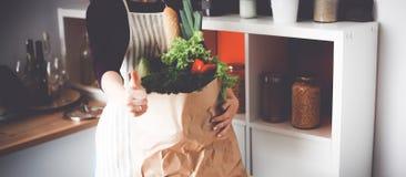 Femme heureuse positive en bonne santé jugeant un panier de papier plein des fruits et légumes Images stock