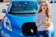 Femme heureuse positive se penchant sur sa voiture Image stock