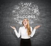 Femme heureuse près d'un croquis de succès sur un tableau noir Photo stock