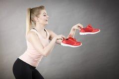 Femme heureuse présent à entraîneurs de vêtements de sport des chaussures photo libre de droits