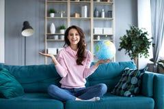 Femme heureuse prévoyant des vacances de voyage ou d'été avec le globe du monde riant et souriant image libre de droits