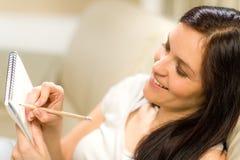 Femme heureuse prenant des notes dans le bloc-notes images stock
