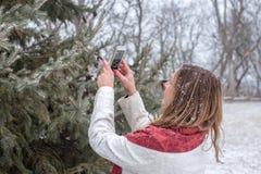 Femme heureuse prenant la photo de la neige tombant sur le pin avec le sma photo libre de droits