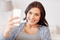 Femme heureuse prenant le selfie avec le smartphone à la maison Photographie stock