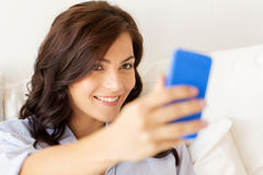 Femme heureuse prenant le selfie avec le smartphone à la maison Image libre de droits