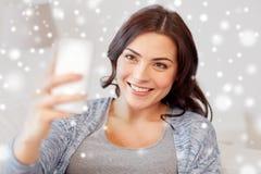 Femme heureuse prenant le selfie avec le smartphone à la maison Photographie stock libre de droits