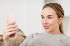 Femme heureuse prenant le selfie avec le smartphone à la maison Photos libres de droits