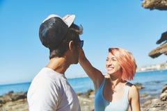 Femme heureuse prenant son chapeau d'ami sur la plage Photographie stock