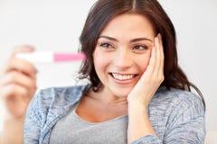 Femme heureuse regardant à la maison l'essai de grossesse image libre de droits
