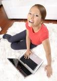 Femme heureuse regardant l'appareil-photo avec l'ordinateur portatif Photos libres de droits
