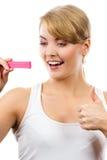 Femme heureuse regardant l'essai de grossesse avec le résultat positif et montrant des pouces  Image stock