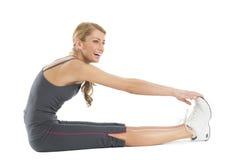 Femme heureuse regardant loin touchante ses orteils Photos stock