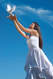 Femme heureuse relâchant un pigeon en ciel Image stock