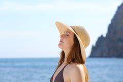 Femme heureuse respirant l'air frais sur la plage avec un chapeau Photo libre de droits