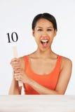 Femme heureuse retardant la carte de score donnant Mark Out Of Ten Photos stock