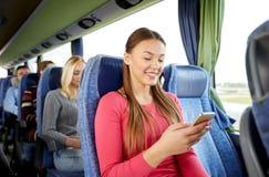 Femme heureuse s'asseyant dans l'autobus de voyage avec le smartphone image stock