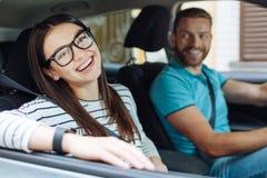 Femme heureuse s'asseyant dans la voiture à côté de son ami Image stock