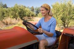 Femme heureuse s'asseyant dans le tracteur Images stock