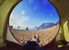 Femme heureuse s'asseyant dans une tente, vue des montagnes Photographie stock