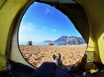 Femme heureuse s'asseyant dans une tente, vue des montagnes Photo libre de droits